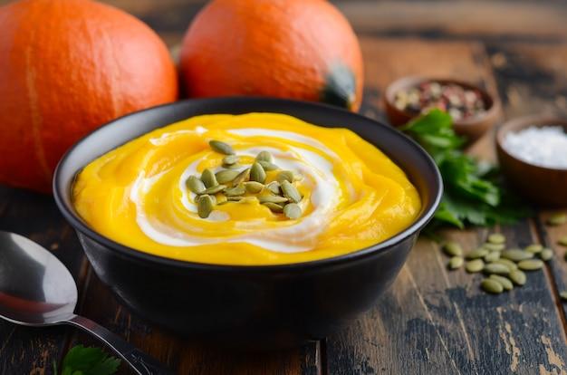 Sopa creme de abóbora com creme e sementes de abóbora na mesa de madeira rústica velha. Foto Premium