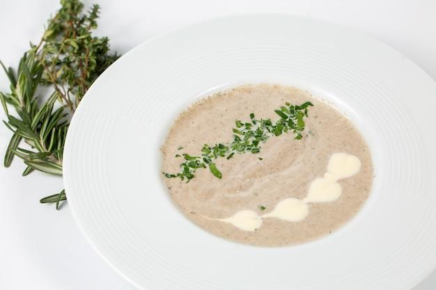 Sopa creme de cogumelos em um prato branco sobre branco Foto gratuita