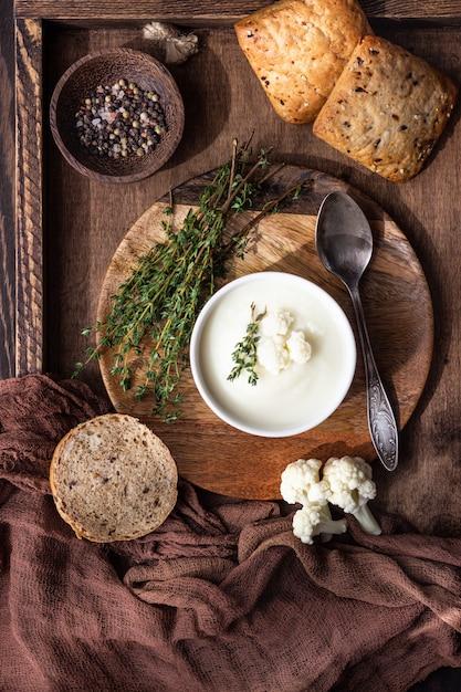 Sopa creme de couve-flor decore com couve-flor fresca, tomilho e pão em uma tigela de cerâmica branca. Foto Premium