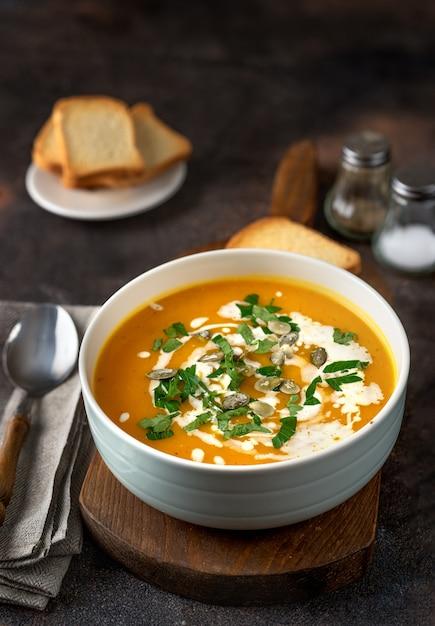 Sopa de abóbora com creme e salsa na mesa rústica escura Foto Premium