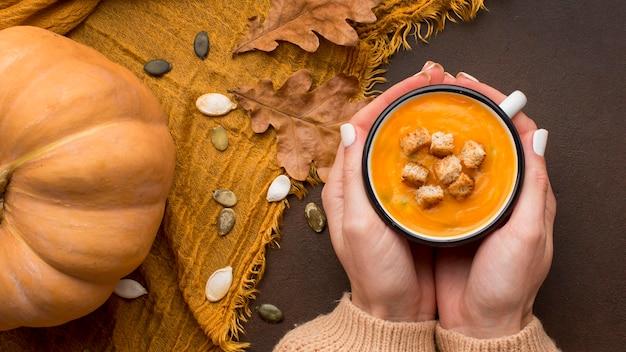 Sopa de abóbora com croutons em uma caneca segura pelas mãos Foto gratuita