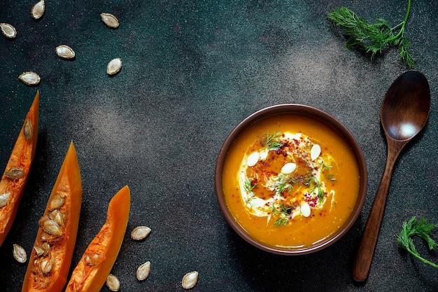 Sopa de abóbora e cenoura assada com creme, sementes e verde fresco na tigela de cerâmica. vista do topo Foto gratuita