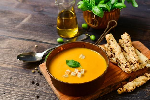 Sopa de abóbora e pão com manjericão e bolachas crocantes, receita vegan Foto Premium