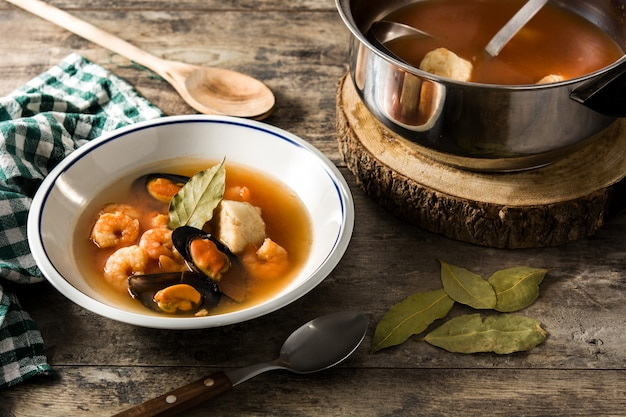 Sopa de bouillabaisse francês na mesa de madeira. Foto Premium