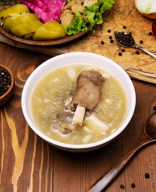 Sopa de carne de borrego com um pedaço de carne, molho de tomate e cebola, sumakh. Foto gratuita