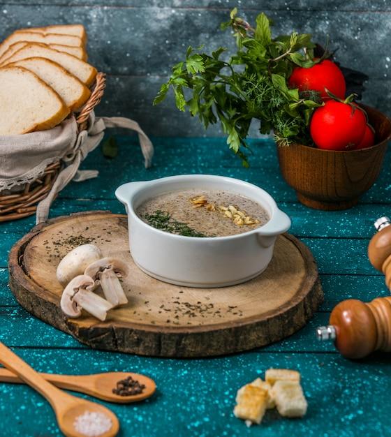 Sopa de cogumelos com nozes na placa de madeira Foto gratuita