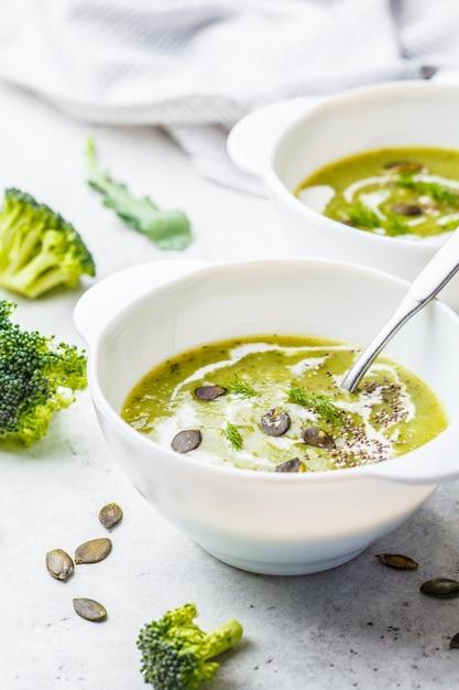 Sopa de creme de brócolis desintoxicação vegan com creme de coco e sementes de abóbora em tigela branca Foto Premium