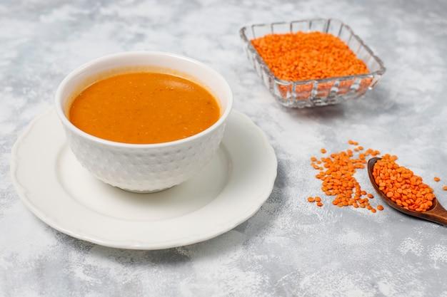 Sopa de creme de lentilha vermelha na luz em uma tigela branca, vista superior Foto gratuita