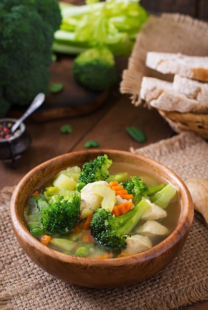 Sopa de galinha com brócolis, ervilha, cenoura e aipo na tigela Foto Premium