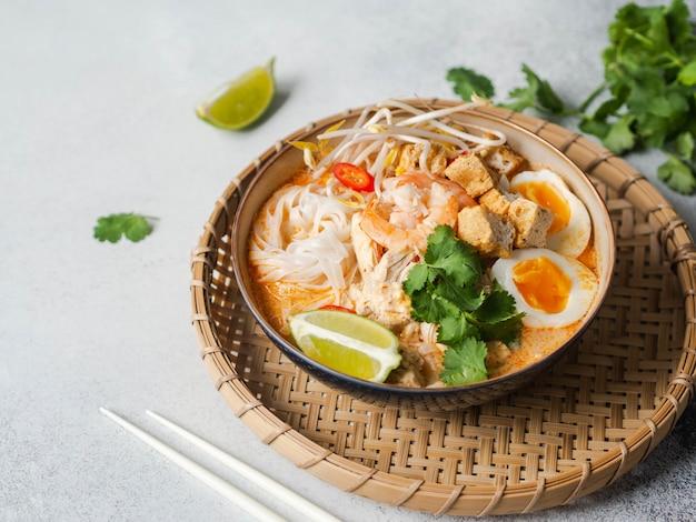 Sopa de laksa de macarrão da malásia com frango, camarão e tofu em uma tigela na superfície cinza. copie o espaço Foto Premium