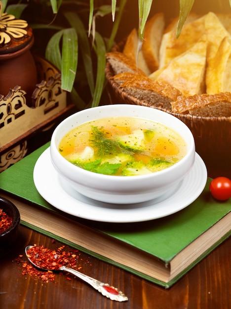 Sopa de legumes caseiros frango, visão aérea em um livro sobre a mesa Foto gratuita