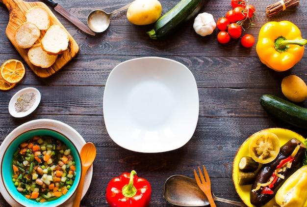 Sopa de legumes fresca, feita em casa, na mesa rústica de madeira, vista superior Foto Premium