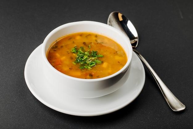 Sopa de lentilha com ingredientes misturados e ervas em uma tigela branca com uma colher. Foto gratuita
