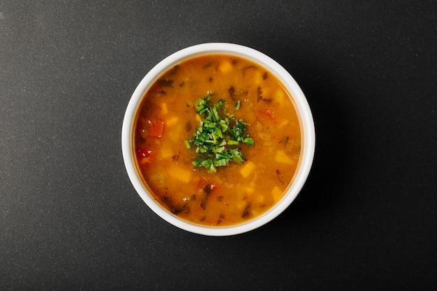 Sopa de lentilha com ingredientes misturados e ervas em uma tigela branca. Foto gratuita