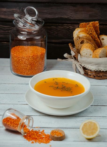 Sopa de lentilha servida com fatias de limão e pão Foto gratuita