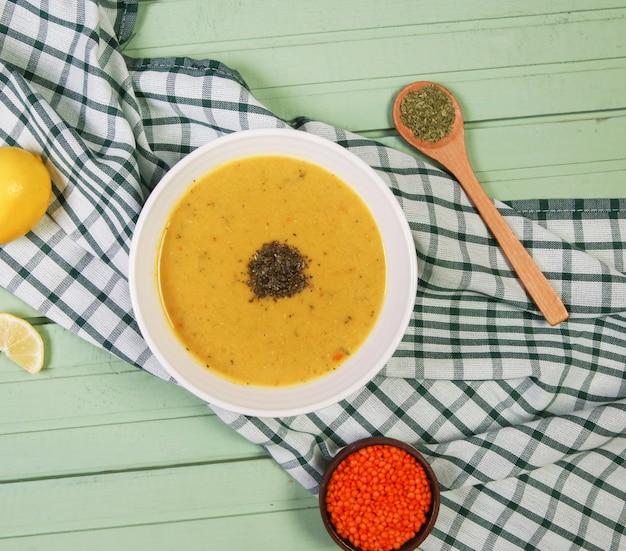 Sopa de lentilha vermelha com ervas na tigela branca sobre a toalha xadrez. Foto gratuita