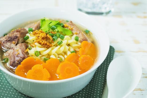Sopa de macarrão com carne de porco e cenoura na mesa de madeira branca Foto gratuita