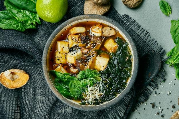 Sopa de miso vegetariana fresca com cogumelos shiitake, queijo tofu e algas em um pano cinza. comida saudável e equilibrada. vista do topo. Foto Premium