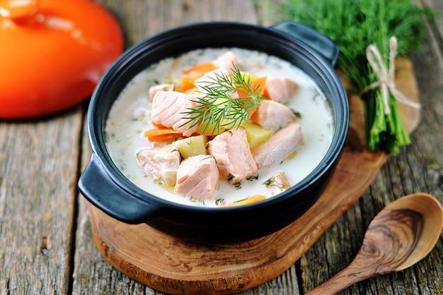 Sopa de salmão com creme em um velho fundo de madeira Foto Premium