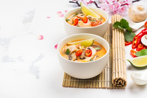 Sopa de tom yum tradicional com ramo de sakura florescendo na mesa de pedra branca Foto Premium