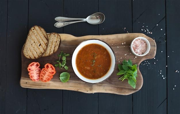 Sopa de tomate assado com manjericão fresco, especiarias e pão na tigela de metal vintage na placa de madeira Foto Premium
