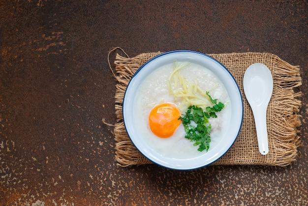 Sopa deliciosa de arroz com carne, ovo e ervas na parede de metal enferrujada com espaço de cópia., comida quente e conceito de refeição saudável Foto Premium