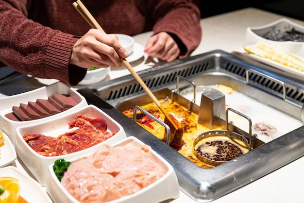 Sopa picante e azeda de shabu de hotpot chinês com carne e frutos do mar, estilo chinês suki - foco seletivo Foto Premium