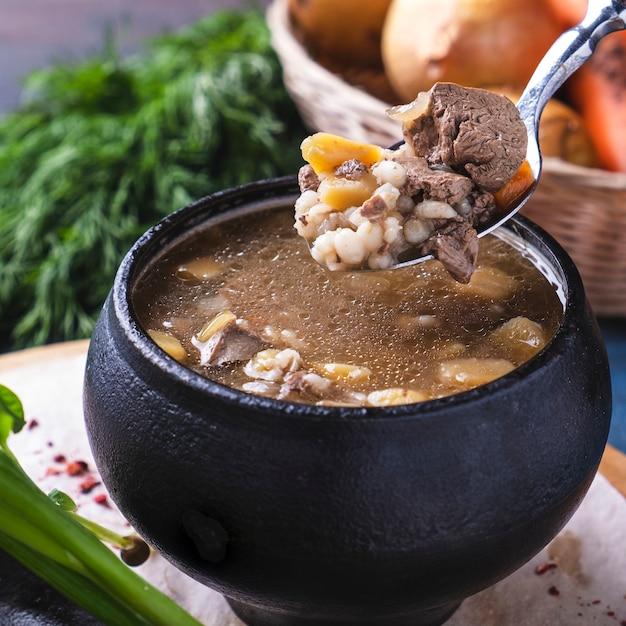 Sopa saborosa de carne e cogumelos em uma panela. fechar-se Foto Premium