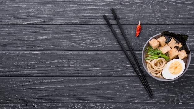 Sopa saudável de ramen vista superior com ovo e pauzinhos Foto gratuita