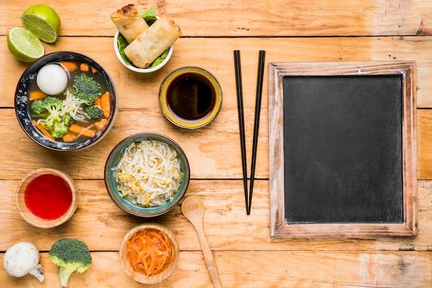 Sopa tailandesa; rolinho primavera; molhos e broto de feijão com pauzinho sobre a mesa de madeira Foto gratuita