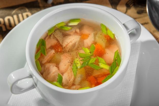 Sopa transparente com frango, cenoura e verduras Foto Premium