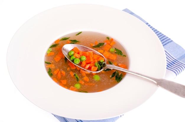 Sopa vegetal dietética com cenouras, ervilhas e cebolas verdes. Foto Premium