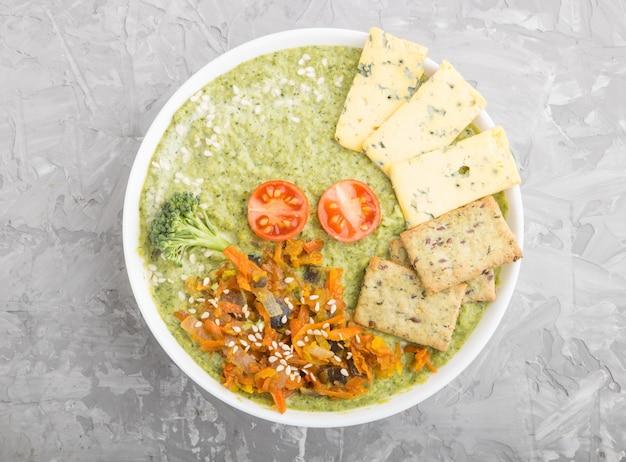 Sopa verde de creme de brócolis com biscoitos na tigela branca, vista superior. Foto Premium