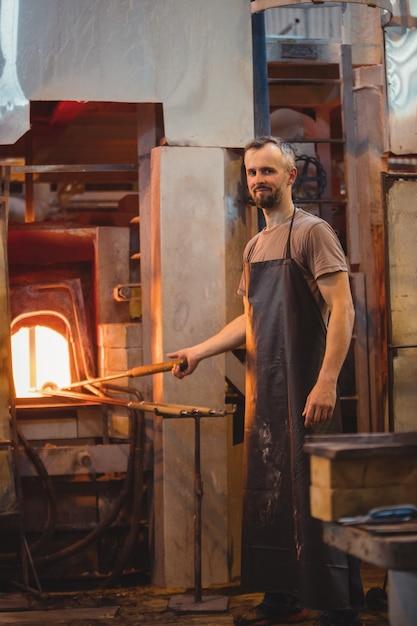 Soprador de vidro aquecendo um copo no forno de sopradores de vidro Foto gratuita
