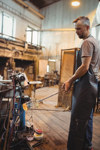 Soprador de vidro moldando um vidro fundido Foto gratuita