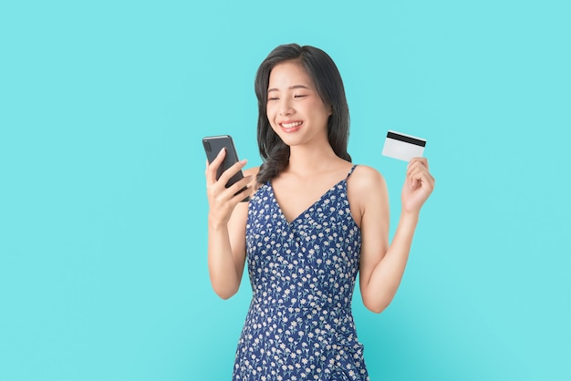 Sorria felizmente mulher asiática segurando smartphone e cartão de crédito, compras on-line sobre fundo azul. Foto Premium