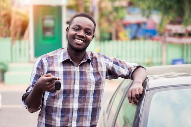 Sorria homem africano com as chaves no carro Foto Premium