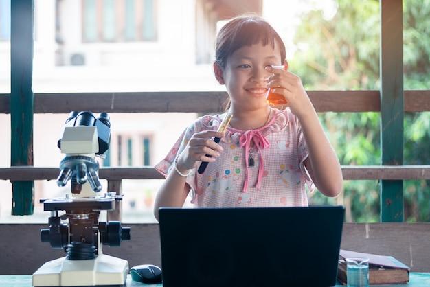 Sorria menina criança aprendendo e fazendo experimentos científicos. conceito de educação escolar em casa. Foto Premium