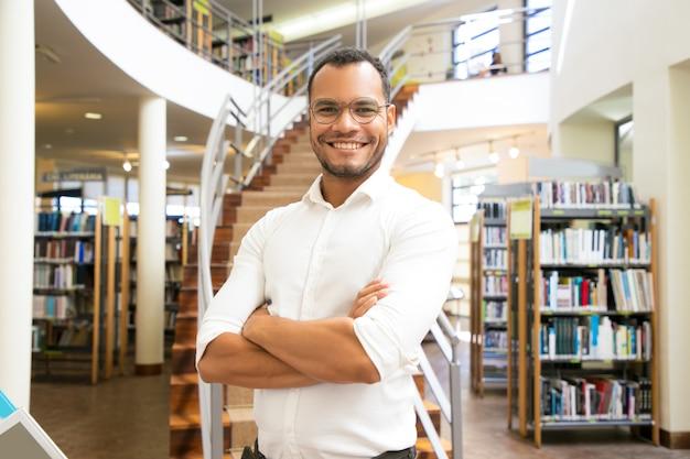 Sorridente homem afro-americano posando na biblioteca pública Foto gratuita