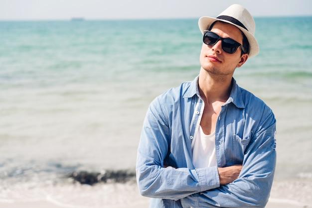 Sorridente homem bonito relaxar em óculos escuros e chapéu de palha na praia tropical. Foto Premium