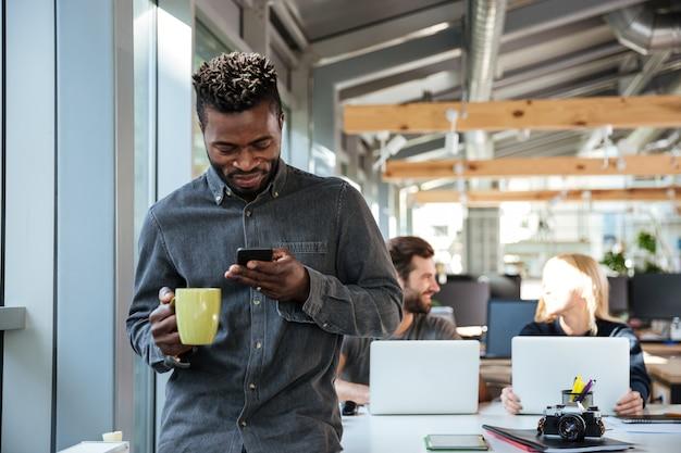 Sorridente jovem africano em pé no escritório conversando por telefone Foto gratuita