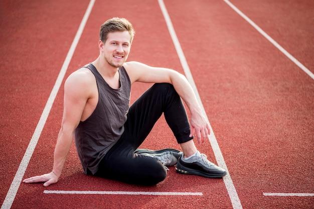 Sorridente jovem atleta do sexo masculino sentado na pista de corrida vermelha, perto da linha de partida Foto gratuita