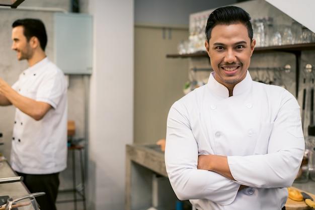 Sorridente jovem chefe asiático no interior da cozinha do restaurante. vintage filtrou a imagem. Foto gratuita