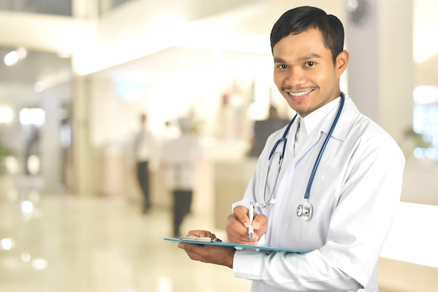 Sorridente jovem médico segurando uma prancheta no hospital Foto Premium