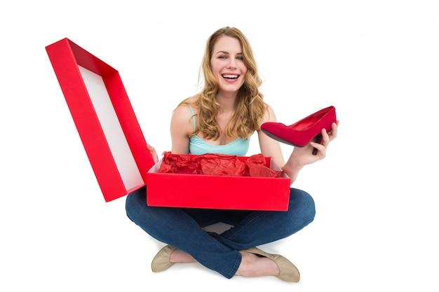 Sorridente jovem mostrando seus novos sapatos Foto Premium