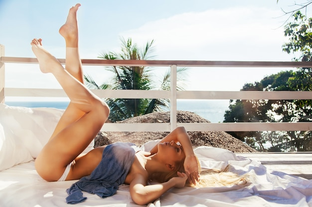Sorridente jovem mulher com belas pernas descansando em um dia ensolarado Foto gratuita