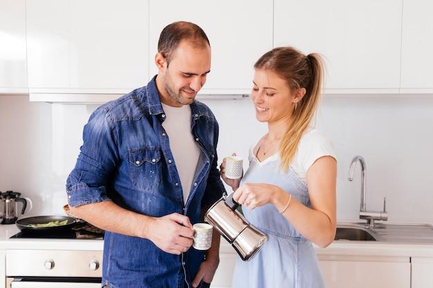 Sorridente jovem mulher derramando café na copa espera por seu namorado na cozinha Foto gratuita