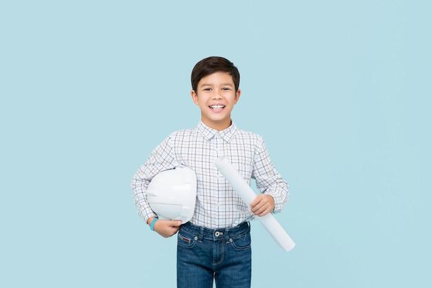 Sorridente jovem rapaz de raça mista asiático aspirando a ser engenheiro segurando blueprint e capacete isolado na parede azul clara Foto Premium