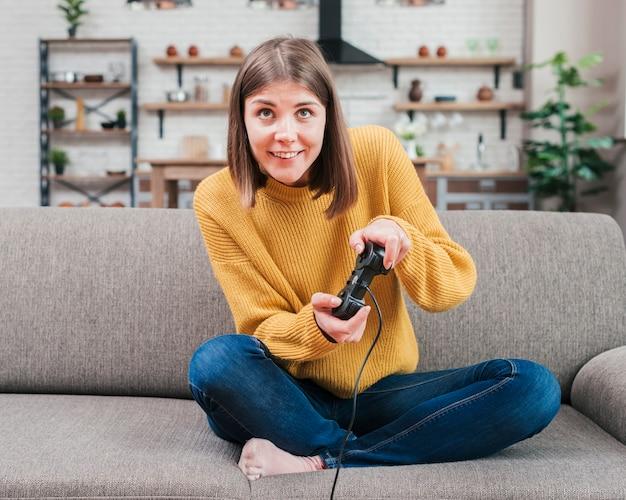 Sorridente jovem se divertindo jogando vídeo game console em casa Foto gratuita