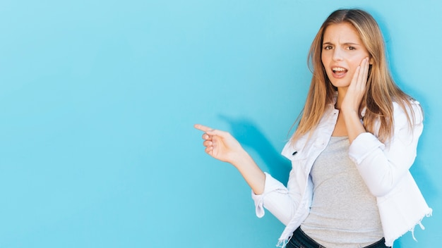 Sorridente jovem tendo dor de dente, apontando o dedo no fundo azul Foto gratuita